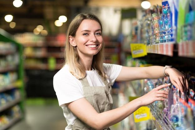 Portret van verkoopster, vrouw die lacht en kijkt naar de camera in de supermarkt. aangename vriendelijke vrouwelijke verkoper die in de winkel tussen de rijen staat. handel bedrijfs- en mensenconcept