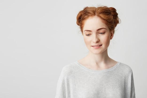 Portret van verlegen jong mooi roodharigemeisje die met broodjes onderaan het glimlachen kijken.