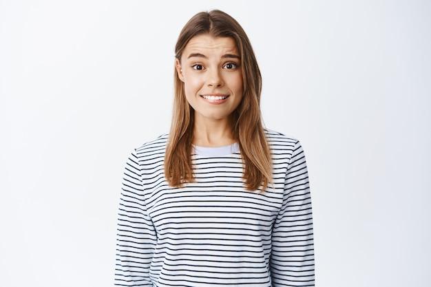 Portret van verlegen nerveus blond meisje dat op lip bijt en ongemakkelijk glimlacht, zich onzeker voelt, opgewonden tegen een witte muur staat