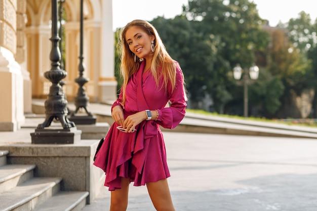 Portret van verleidelijke blonde vrouw in elegante zijden jurk
