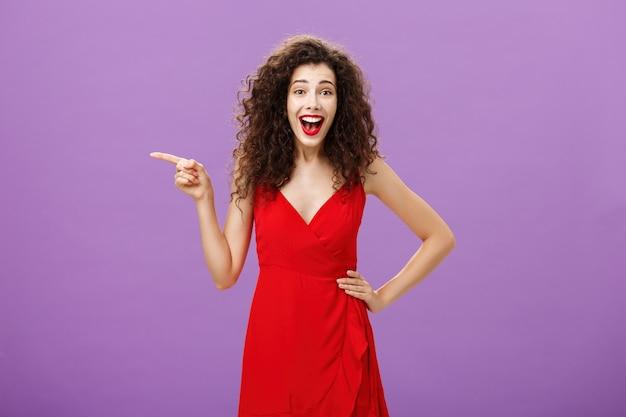 Portret van vermaakte en geamuseerde vrolijke europese vrouw met krullend kapsel in rode avondjurk lachend van amusement en vreugde wijzend naar links vermaakt poserend over paarse achtergrond.