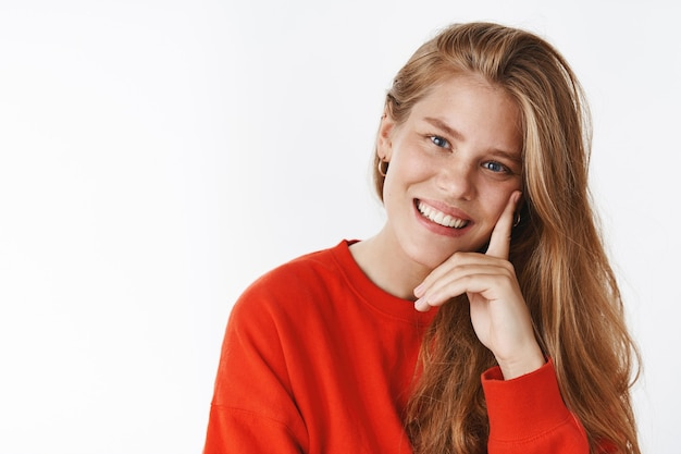 Portret van vermaakte zorgeloze mooie jonge vrouw met sproeten en blauwe ogen leunend hoofd op vinger gedrukt op wang glimlachend en lachend deelnemend aan gesprek vriendelijk en vrolijk