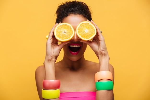 Portret van vermakelijke afro-amerikaanse vrouw met mode-accessoires plezier en die de ogen bedekt met twee geïsoleerde helften van sinaasappel, over gele muur