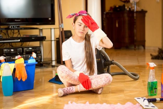 Portret van vermoeid tienermeisje dat houten vloer schoonmaakt in de woonkamer living