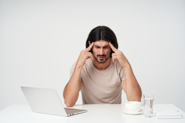 Portret van vermoeide, beklemtoonde zakenman met zwart haar en baard. kantoor concept. zijn slapen masseren. lijdt aan hoofdpijn. zittend op de werkplek, geïsoleerd over witte muur