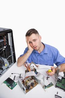 Portret van vermoeide computeringenieur met cpu-delen