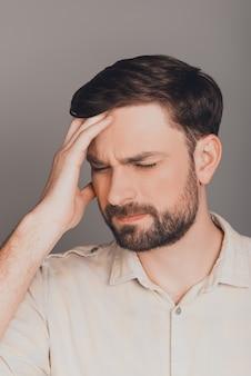Portret van vermoeide depressieve jongeman met sterke hoofdpijn