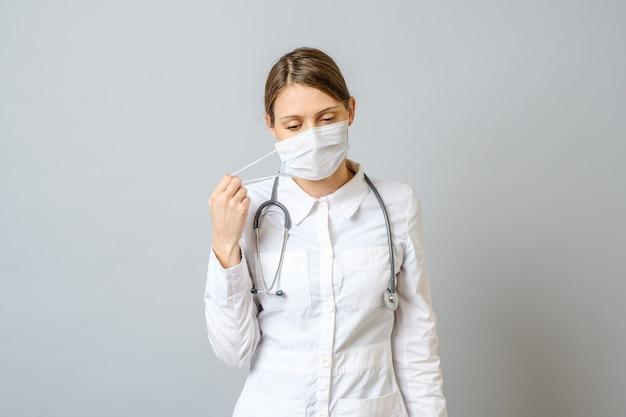 Portret van vermoeide jonge arts die medisch gezichtsmasker opstijgen dat over grijze muur wordt geïsoleerd