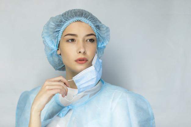 Portret van vermoeide jonge arts die medisch gezichtsmasker opstijgt dat over grijze achtergrond wordt geïsoleerd