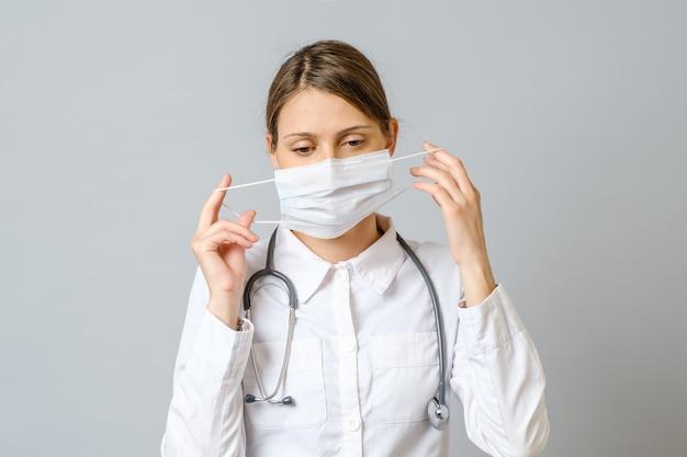 Portret van vermoeide jonge arts medische gezichtsmasker opstijgen