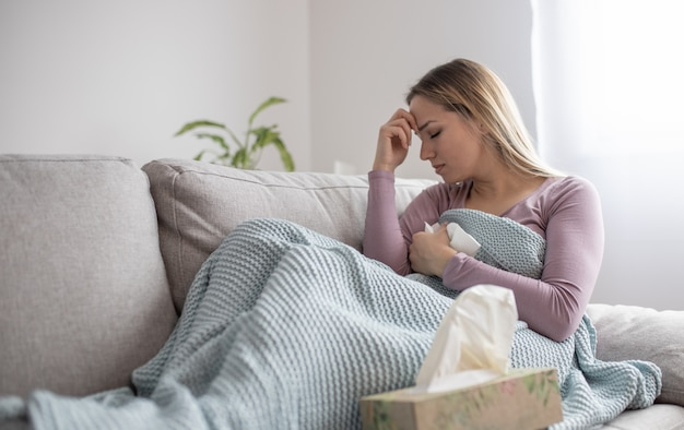 Portret van vermoeide jonge vrouw die aan hoofdpijn lijdt
