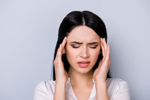Portret van vermoeide mooie jonge vrouw met zwart haar die aan hoofdpijn op grijze ruimte lijdt
