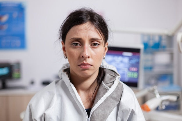 Portret van vermoeide tandarts in beschermende kleding tegen coronavirus