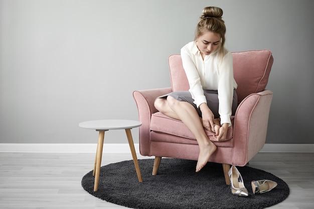Portret van vermoeide uitgeputte jonge vrouwelijke kantoormedewerker in formele slijtage zittend in een fauteuil en masseert haar voet om pijn te verlichten vanwege het dragen van schoenen met hoge hakken de hele dag. gezondheid en welzijn