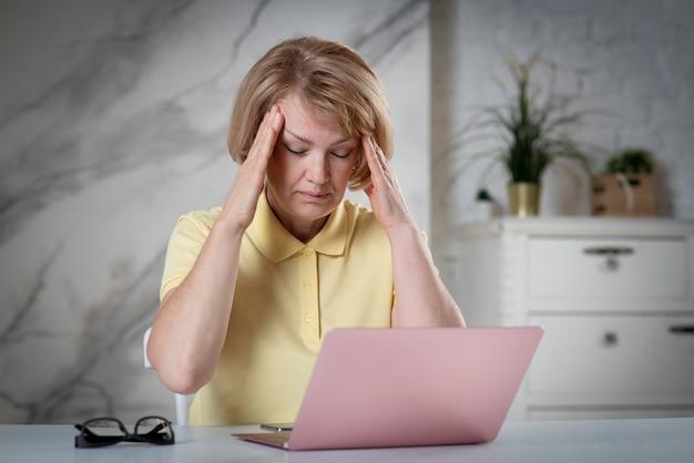 Portret van vermoeide uitgeputte oudere senior vrouw, dame voelt zich ziek, ziek met hoofdpijn of migraine en houdt haar hoofd vast met handen zittend op tafel met laptopcomputer met gesloten ogen. overwerkt