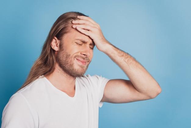Portret van vermoeide zieke jonge man met sterke migraine geïsoleerd