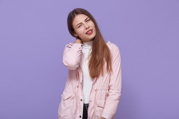 Portret van vermoeide zieke vrouw met mooi haar in jas staande tegen lila muur, nekpijn voelen, gespannen spieren masseren, kijkt naar de camera.