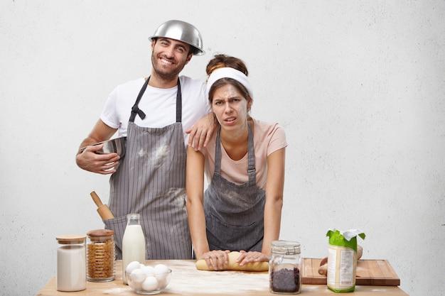 Portret van vermoeidheid, slordig vrouwtje kneedt gebak, kijkt met vermoeide uitdrukking, brengt de hele dag door op keuken en echtgenoot die ondersteunt en helpt