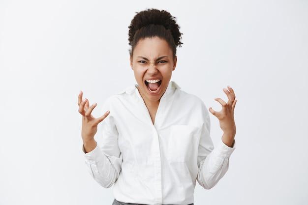 Portret van verontruste geïrriteerde verontwaardigde afro-amerikaanse vrouw, die zich intens voelt, schreeuwend en fronsend wil doden