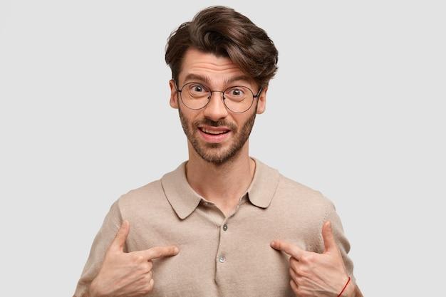 Portret van verontwaardigde jonge man wijst naar zichzelf, verbaasd om gekozen te worden voor het presenteren van projectwerk, draagt een bril, geïsoleerd over witte stuidomuur