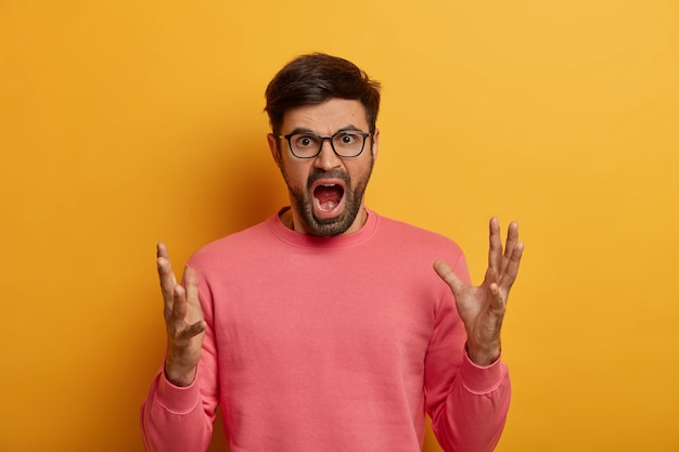 Portret van verontwaardigde man staat in woedend gebaar, schreeuwt luid