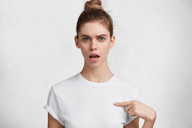 Portret van verontwaardigde mooie blauwe ogen vrouw met haarknoop, gedronken in casual wit t-shirt, geeft aan op lege ruimte voor uw logo of promotietekst, geïsoleerd op een witte achtergrond.