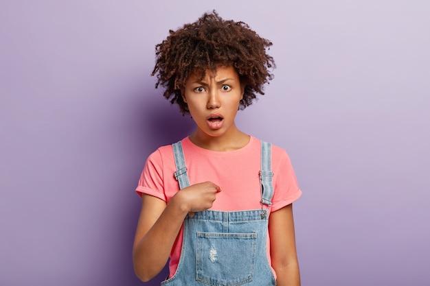 Portret van verontwaardigde ontevreden vrouw met donkere huid wijst naar zichzelf, heeft een verbaasde uitdrukking, vraagt waarom ik, beschuldigd van iets, t-shirt en overall draagt modellen binnen heeft een negatieve reactie