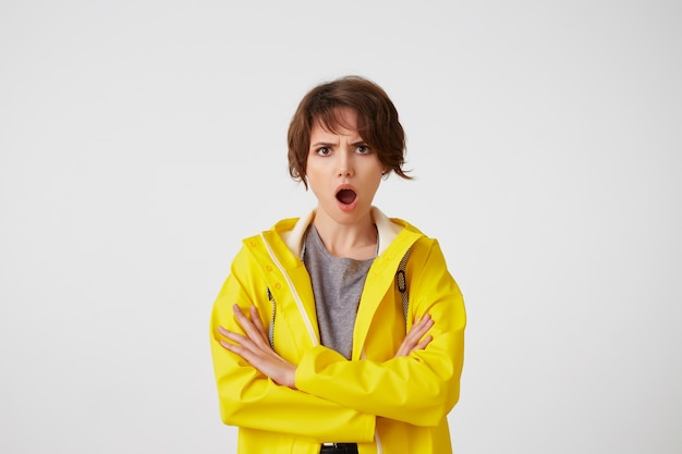 Portret van verontwaardigde schattige vrouw in gele regenjas, kijkt naar de camera met verwonderde uitdrukkingen, met wijd open mond en gekruiste armen, ziet er ontevreden uit, staat over een witte muur.