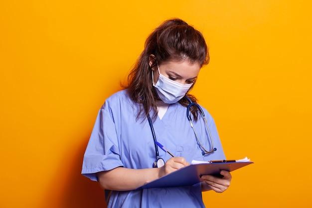 Portret van verpleegster die gezichtsmasker draagt en aantekeningen maakt