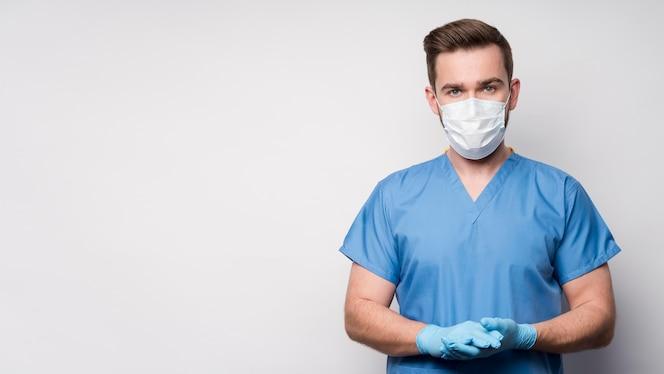 Portret van verpleegster die medisch masker en handschoenen draagt
