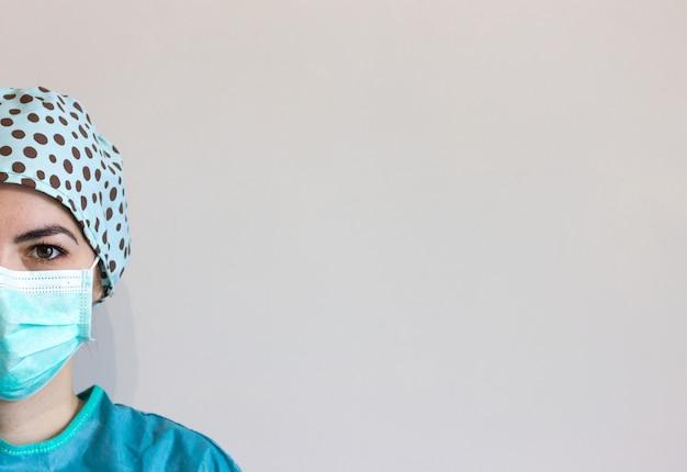 Portret van verpleegster met hygiënisch gezichts chirurgisch medisch masker en toga.