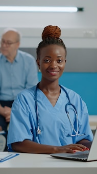 Portret van verpleegster typen op laptop toetsenbord in medische kantoor