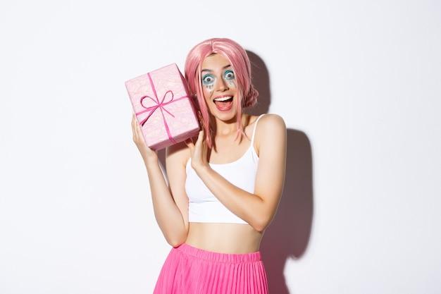 Portret van verrast aantrekkelijk meisje dat opgewonden kijkt, cadeau krijgt voor verjaardag, roze pruik draagt, staand.