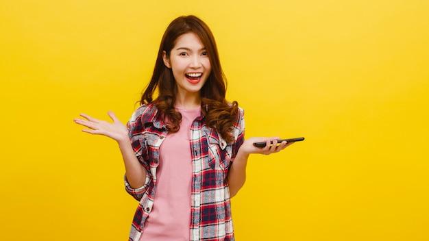 Portret van verrast aziatische vrouw met behulp van mobiele telefoon met positieve expressie, gekleed in casual kleding en camera kijken op gele muur. de gelukkige aanbiddelijke blije vrouw verheugt zich succes.