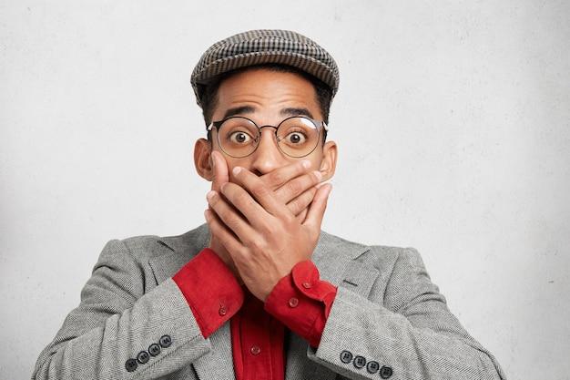 Portret van verrast bezorgd man in bril heeft betrekking op mond met beide handen,