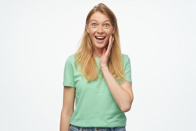 Portret van verrast blonde jonge vrouw, draagt groen t-shirt, starend in de camera met wijd geopende ogen en geschokt gelaatsuitdrukking, houdt haar handpalm op chick