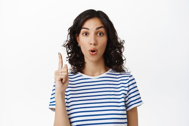 Portret van verrast brunette modern meisje, hap naar adem en zeg wauw, wijzend op advertentie, interessante promo-deal tonen, vertellen over kortingen, staande op wit