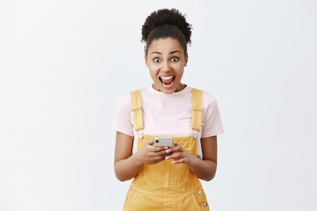Portret van verrast en verbaasd knap meisje met donkere huid in gele overall, schreeuwend en met smartphone