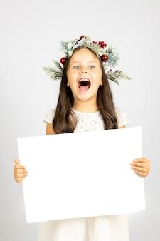 Portret van verrast enthousiast meisje met open mond in kerstkrans met witte lege poster...