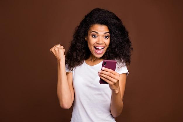 Portret van verrast geschokt afro-amerikaans meisje mobiele telefoon gebruiken lezen sociale media nieuws winnen loterij onder de indruk schreeuw wow omg vuisten heffen draag casual stijl outfit.