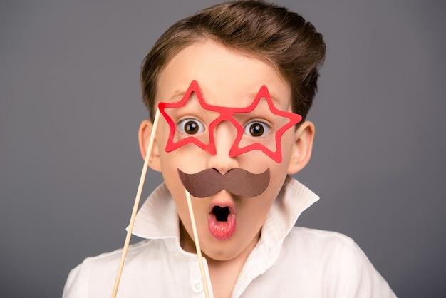 Portret van verrast grappige schooljongen met rekwisieten close-up