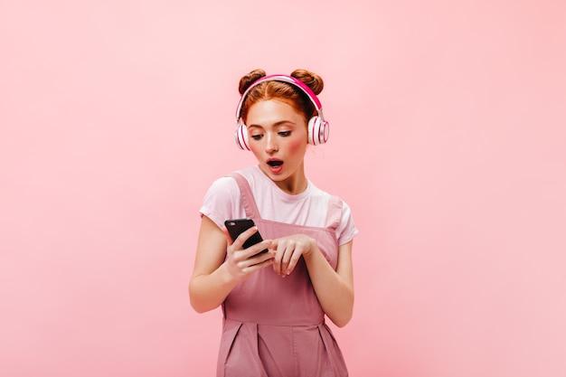 Portret van verrast groenogige vrouw gekleed in roze jurk. vrouw met smartphone en luisteren naar liedjes in de koptelefoon.