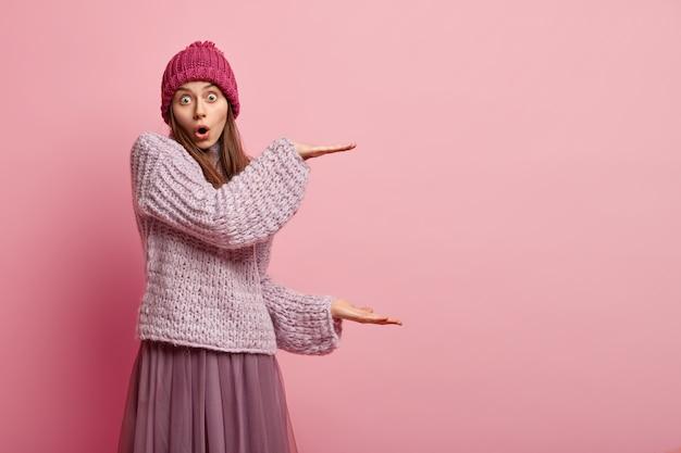 Portret van verrast jong vrouwelijk model vormt groot object met beide handen, onder de indruk van de grootte, gekleed in hoed, trui en lange rok, geïsoleerd over roze muur. mensen en meetconcept