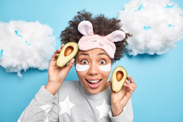 Portret van verrast jonge afro-amerikaanse vrouw poses in nachtkleding houdt twee helften van avocado toepast beauty pads onder ogen kijkt geschokt voorzijde geïsoleerd over blauwe muur