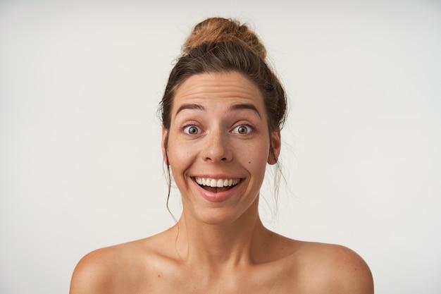 Portret van verrast jonge mooie vrouw met casual kapsel staande op wit met opgetrokken wenkbrauwen en verbaasd gezicht