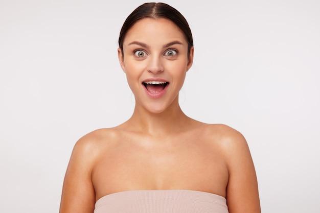 Portret van verrast jonge schattige brunette vrouw met casual kapsel ogen afronden terwijl kijken en houden mond wijd geopend, geïsoleerd