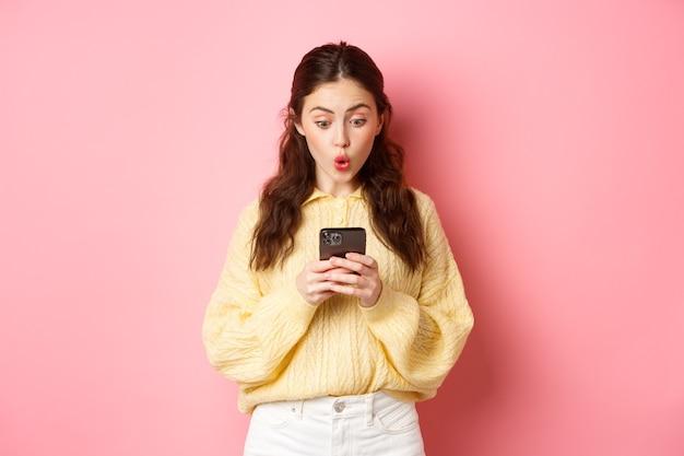Portret van verrast jonge vrouw die bericht leest op smartphone en zeg wow, kijk nieuwsgierig naar mobiel scherm, staande tegen roze muur.