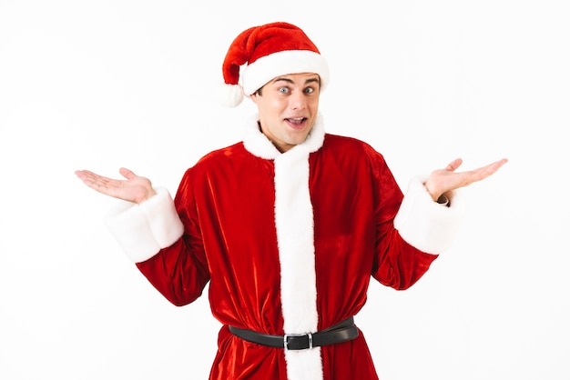 Portret van verrast man 30s in kerstman kostuum en rode hoed handen overgeven