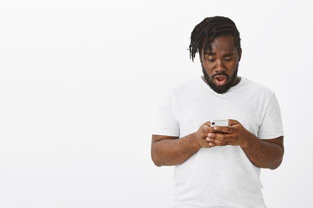 Portret van verrast man met vlechten poseren tegen de witte muur met zijn telefoon
