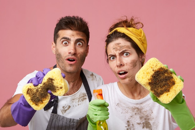 Portret van verrast mannetje en vrouw die met wijd geopende ogen kijken die slordige gezichten en kleren hebben